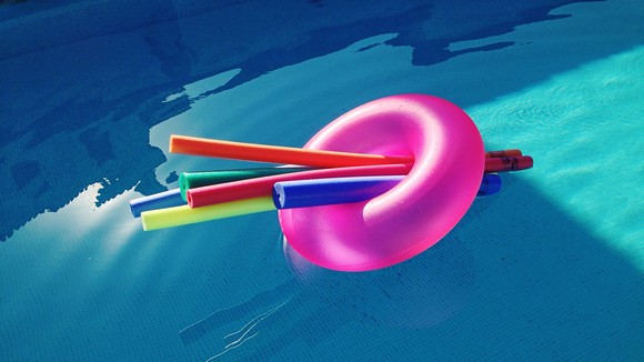 High Angle View Of Pool Noodle And Inflatable Ring Floating On Swimming Pool